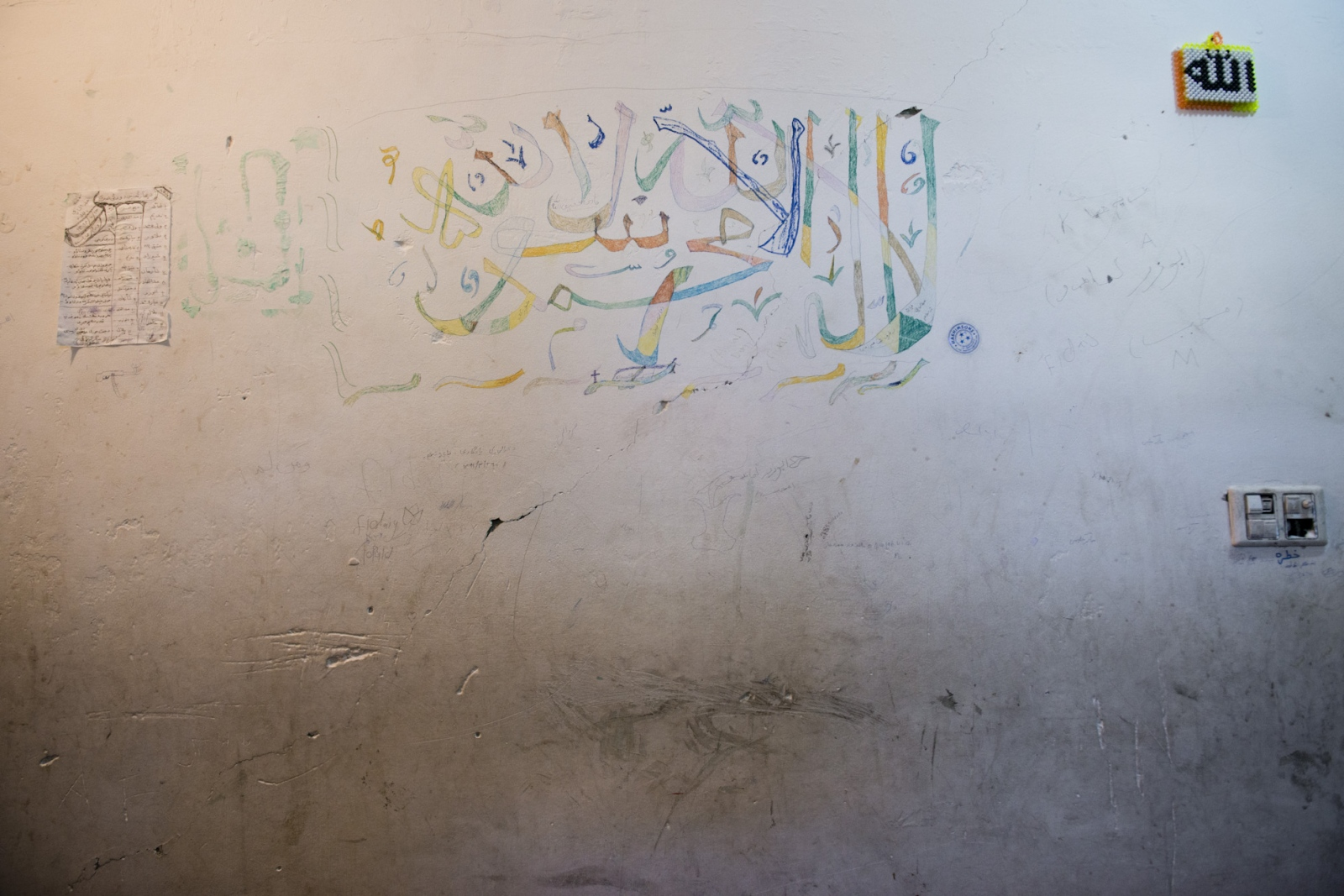 NANGARHAR, AFGHANISTAN | 2015-12-02 | The writing on the wall of a call where to child political prisoner, meaning that they were recruited by Taliban, inside Jalal Abad juvenile rehabilitation centre.