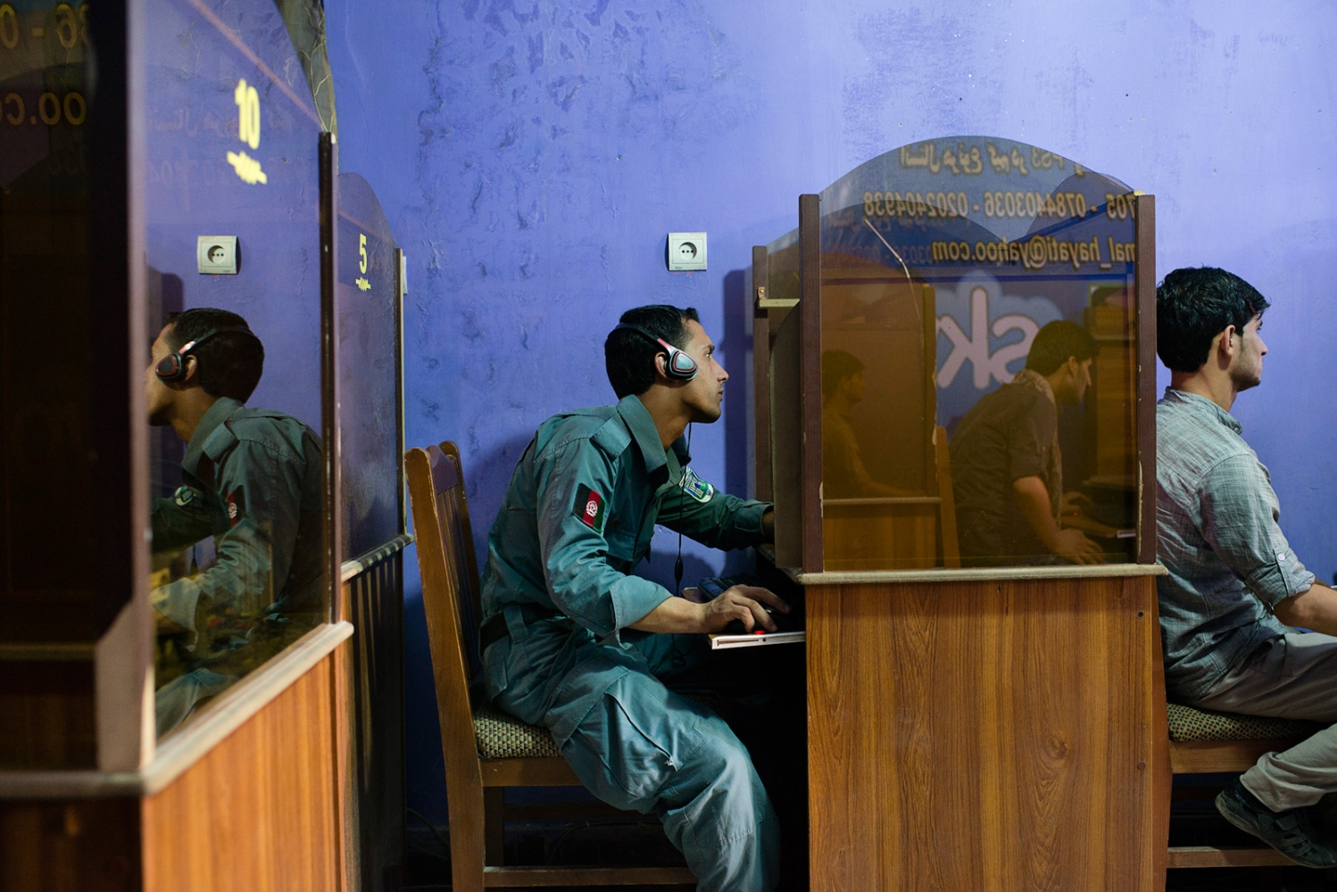 KABUL, AFGHANISTAN | 2014-08-10 | A young Afghan policeman uses a computer on his spare time to check his Facebook account at an internet cafe in Goolaei, northern Kabul.