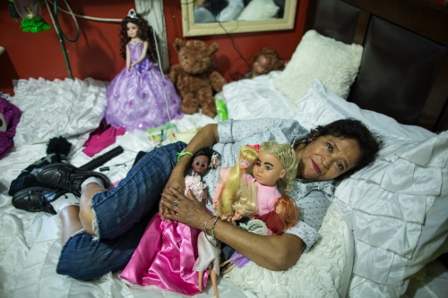 "Irma Verduzco in her house hugging her dolls. ""I grew up being an orphan in the streets, when I was a child I longed for a doll, a toy and, I never had it, that's why I love sleeping surrounded by my dolls, even though I'm old"" says Irma, Sunset Park, Brooklyn, New York, 2016"
