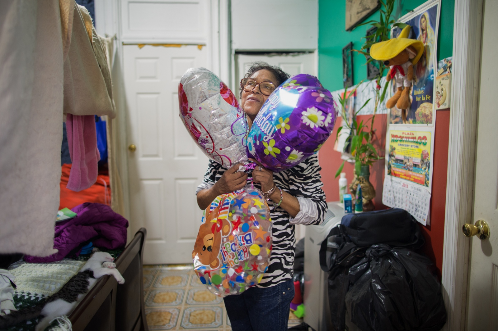 Irma in her house surrounded by balloons that were given to her by her children and grandchildren for her 65th. birthday. Sunset Park, Brooklyn, New York. 2016.