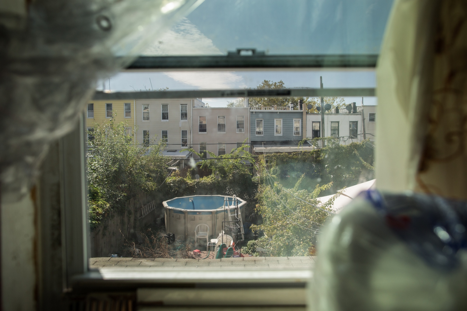 """Dionisia has lived in New York for almost 20 years, """"I have lived in different apartments but always in the neighborhood of Sunset Park, which is where most of my country people of Puebla live,"""" says Dionisia while she is looking from her kitchen window of her apartment. Sunset Park, Brooklyn, New York, 2016."""