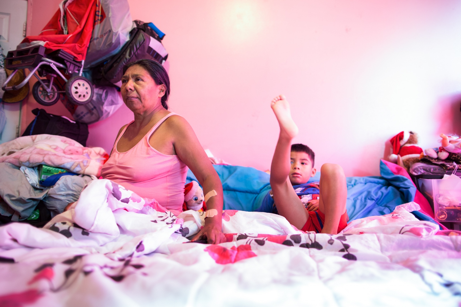 """Dionisia Guadalupe watching television and taking care of her grandson Oscar. Dionisia is 56 years old and has 4 grandchildren, two in Mexico and two in New York with whom she lives. """"For me to be a grandmother is a beautiful thing, children fill me with love, they give me life,"""" says. Sunset Park, Brooklyn, New York, 2016"""