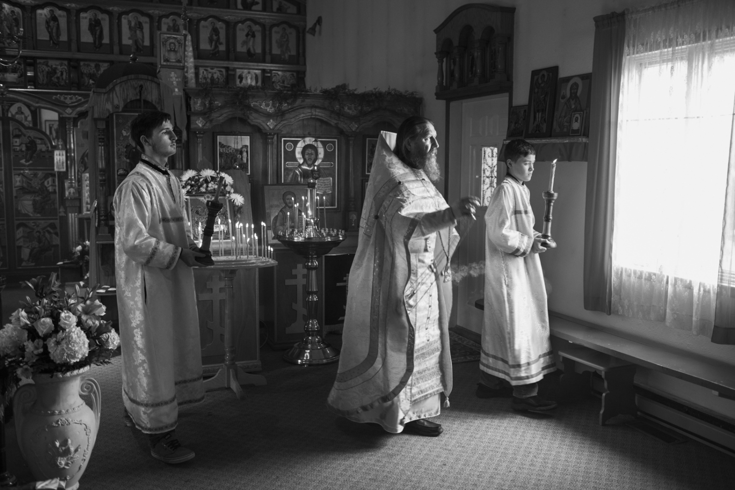 Inside the church of Saint Nicholas, Father Nikolai Yakunin blesses parishioners during Pascha, which begins at midnight and ends at dawn. The smoke of the incense is said to lift prayers to heaven.