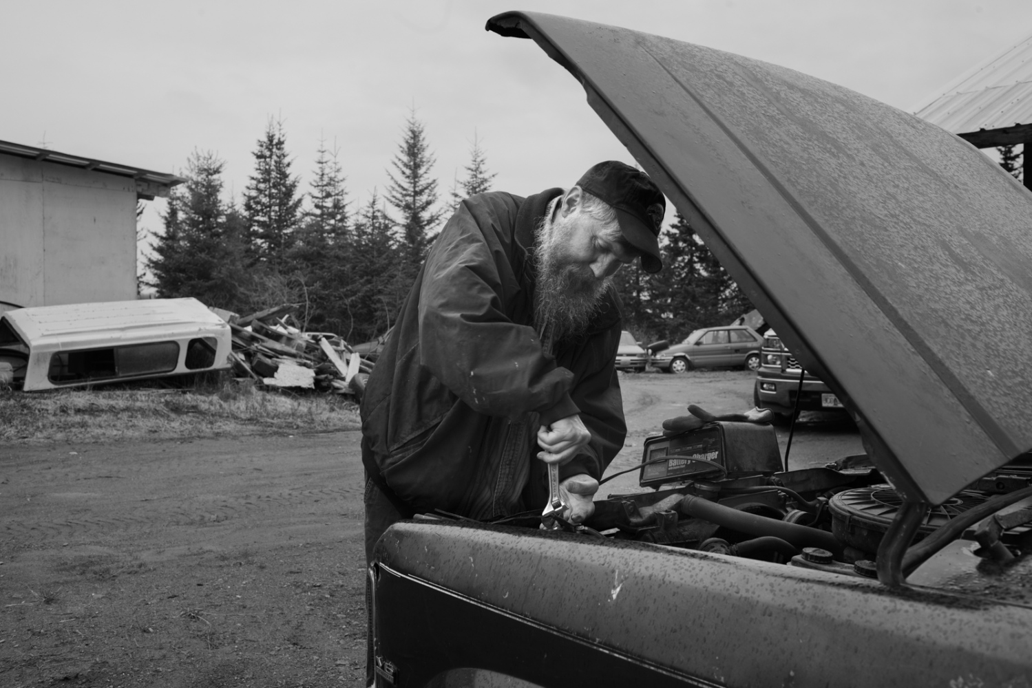 Dennis Fefelov, son of Father Kondraty Fefelov, arranging his engine's car. He used to be a fishermen and was always fetching his motors. Today his industry labour has been relegated to a second level due to an elevating  arthritis and reuma illnes. Dennis is 52 years old.