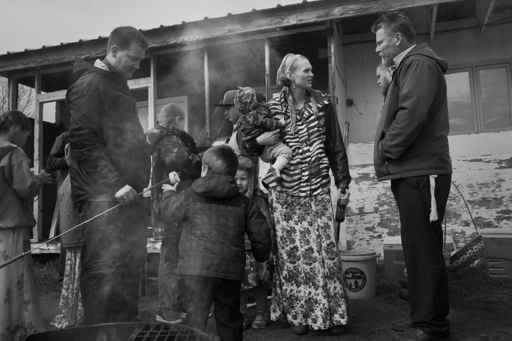 Barbecue around Saint Nicholas church the day after Pascha . Vasilissa Melkomukov stands in the middle holding her son Leo. During the holiday families gather whilst grilling sausages, marshmellows and children play.