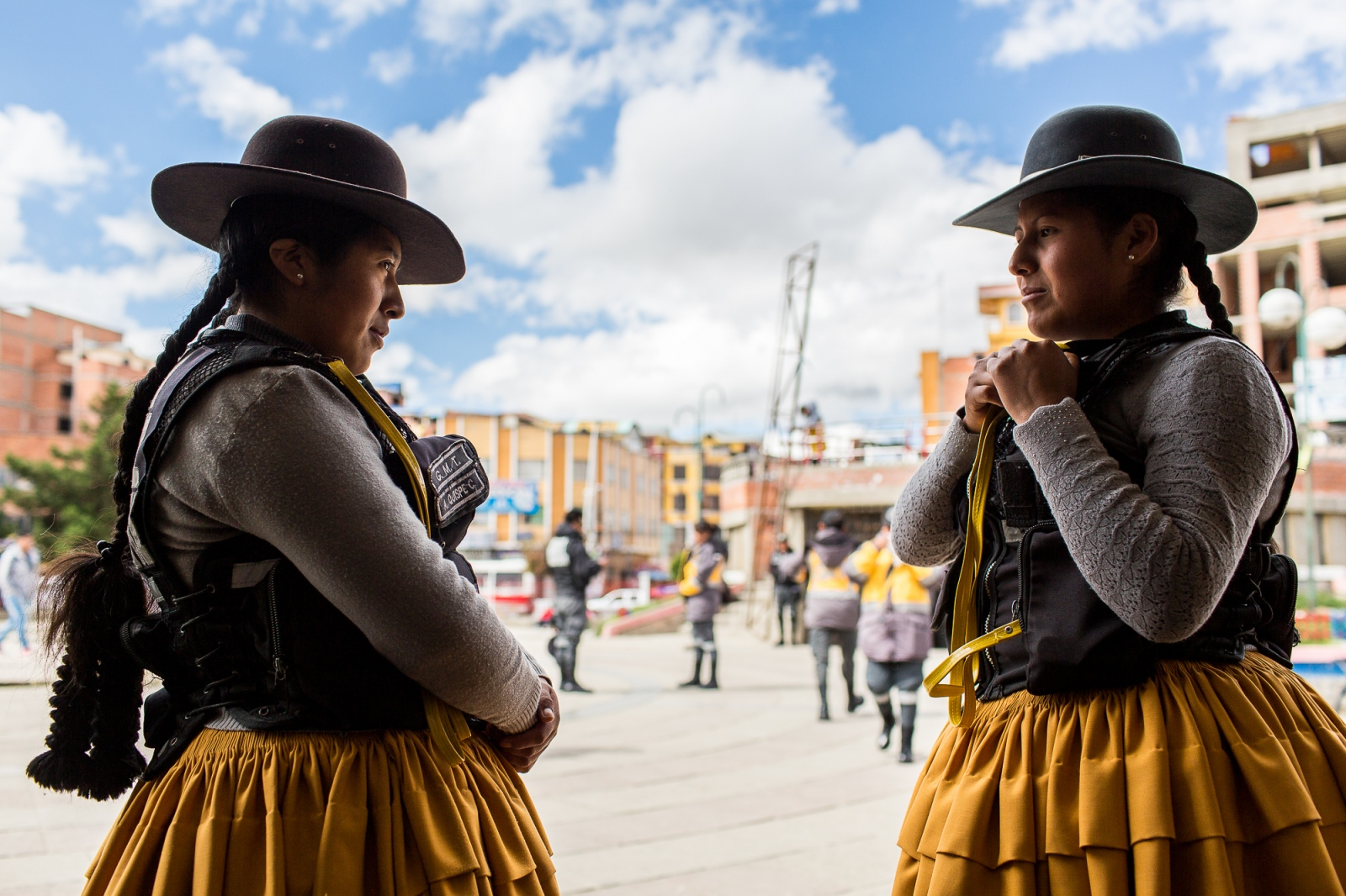 "Estela Loyaza (right) talks with A. Quispe, a fellow traffic warden in El Alto. Estela is one of the 15 ""cholitas"" who work as traffic wardens in the city. Since 2013, the municipality government has been hiring cholitas to control the chaotic traffic of the city."