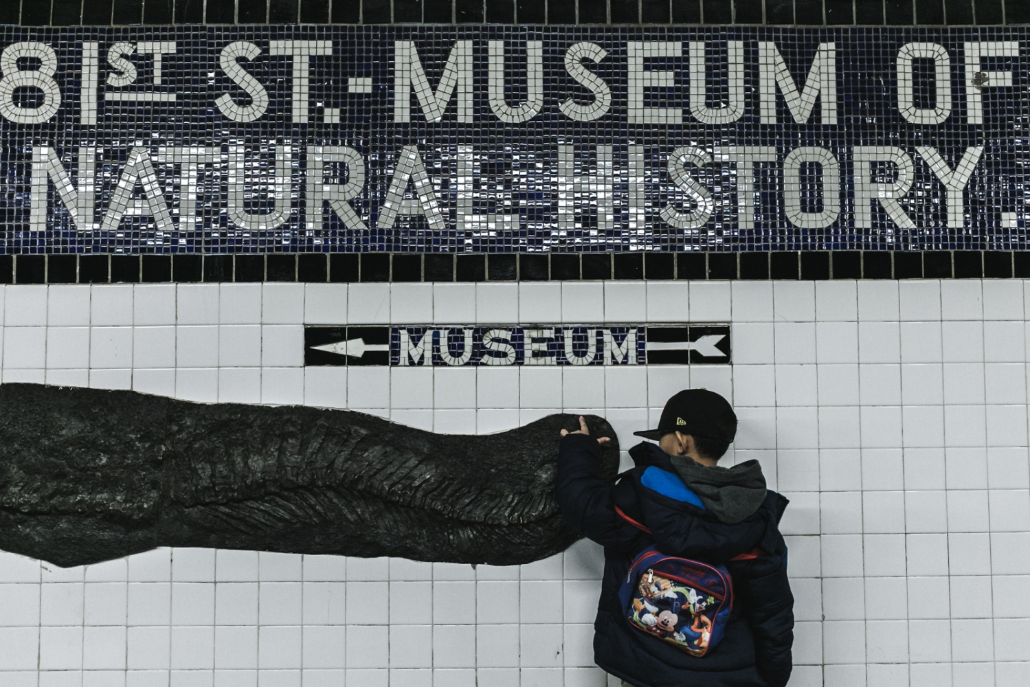 Jayden stands on the subway platform as he prepares to go to the Museum of Natural History in New York City.