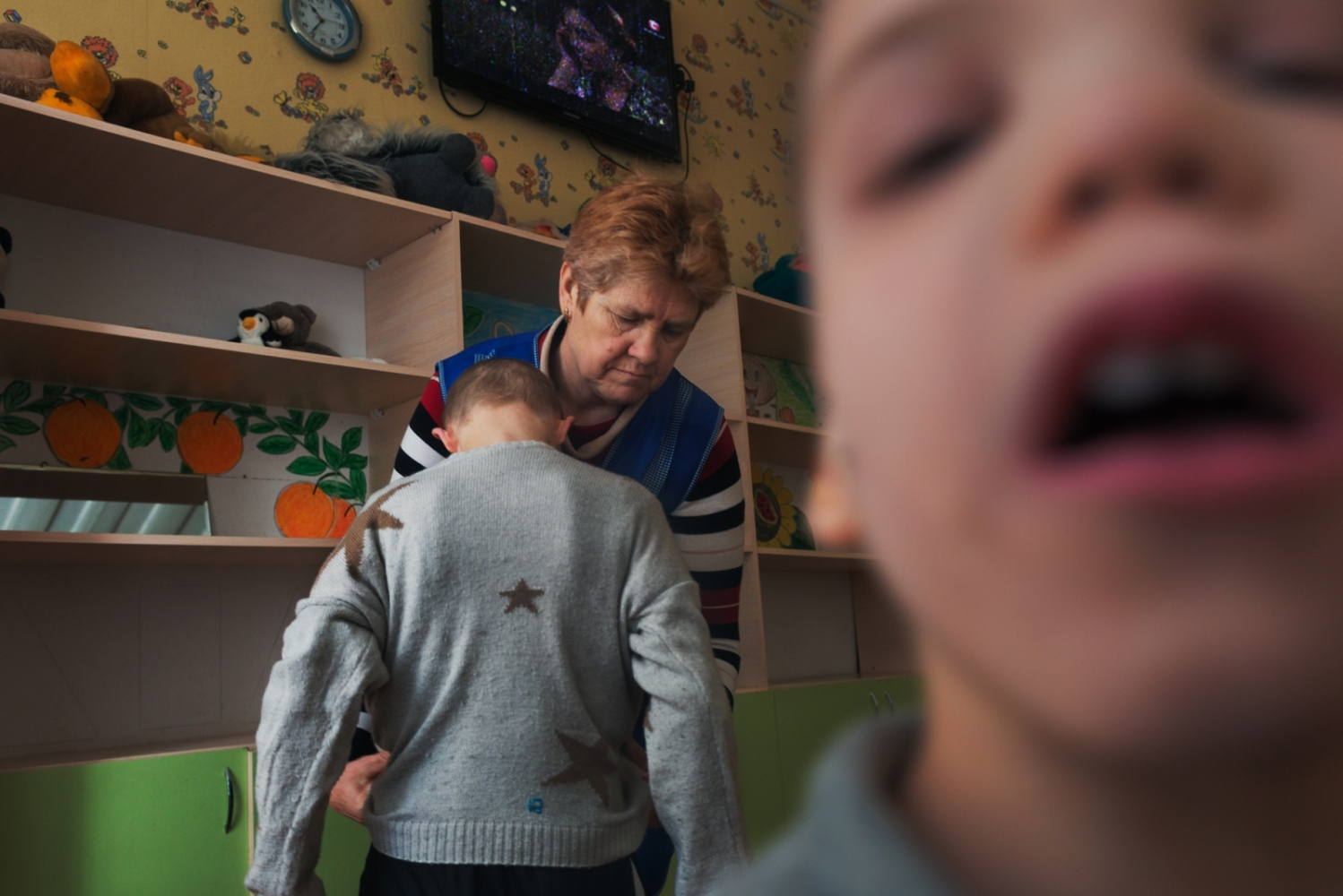 A nanny changes a boy after he urinated himself. The majority of the nannies carry out their duties in a matter of fact way, offering little in the way of compassion.