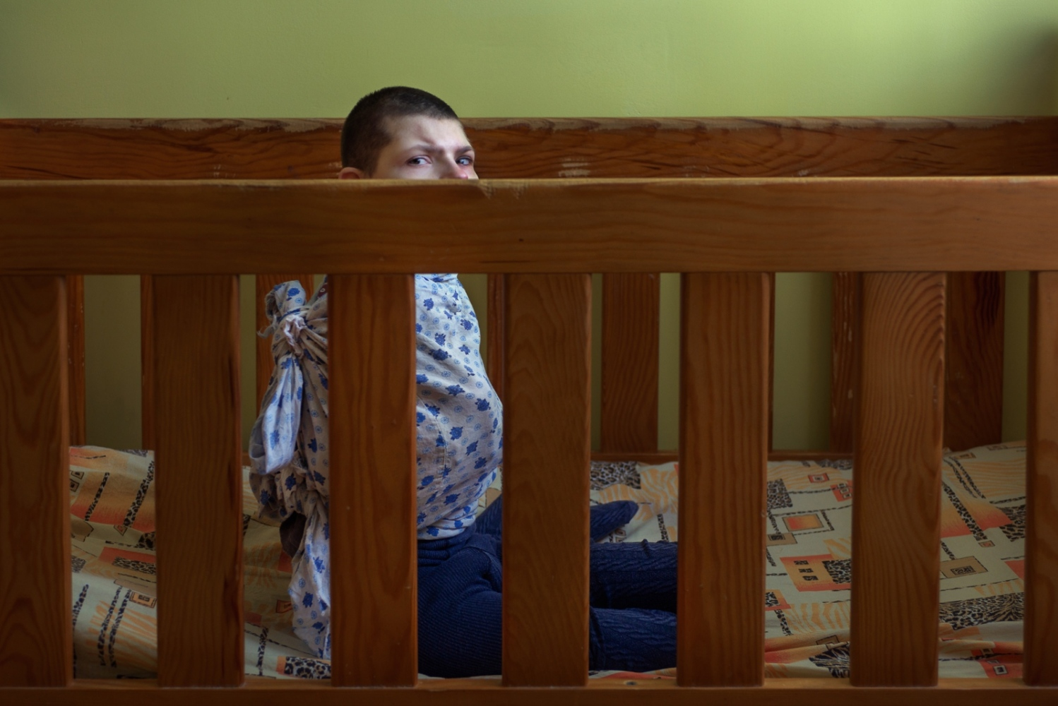 A teenage girl sits in her bed restrained in a homemade starihght jacket.