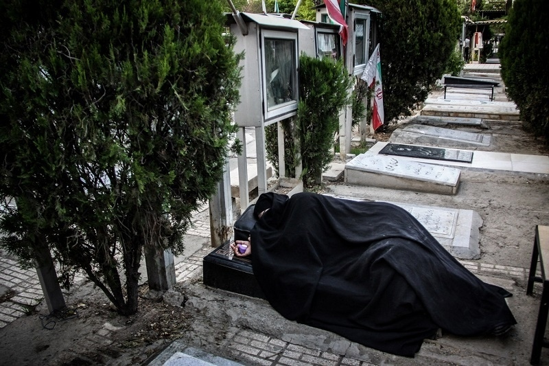 The people of Iran believe that the martyr is alive and holy and they Helps people lives . because of that , in the most important events or weekends , people always going to the cemetery of martyrs and praying and living with iranian martyrs . A member of martyrs family is slept on the grave of a martyr. © Fatemeh Behboudi