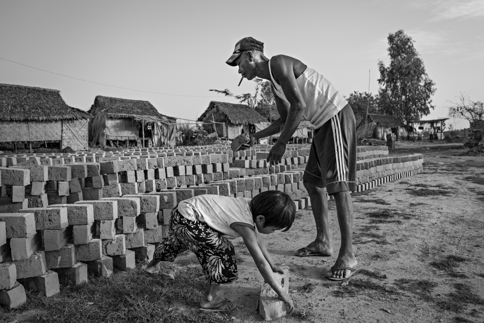 Naing Lin and Saung Ning Wai stack bricks to dry in the sun. Naing Lin often became angry at Saung Ning Wai for reasons that were not readily apparent. Moments of closeness, or times when they worked as a pair, were rare.