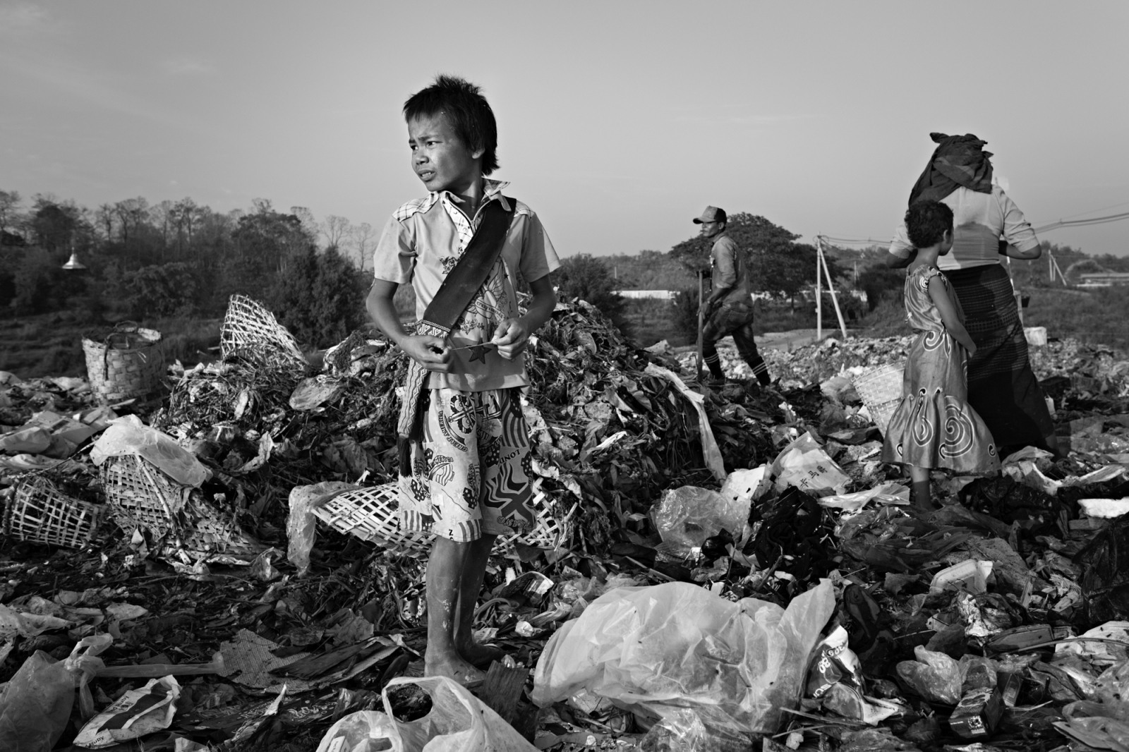 Naing Lin Oo scrounges through a trash pile after work, attempting to find something valuable to sell so that he can earn some cash for himself.