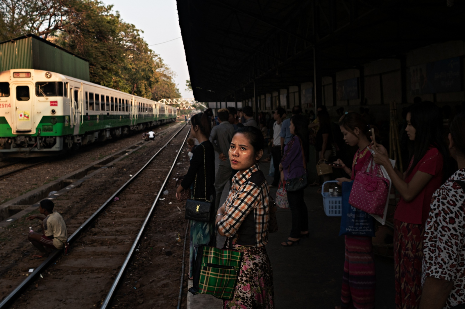 A young woman waits for the train at Bogyoke Aung San station in Yangon.