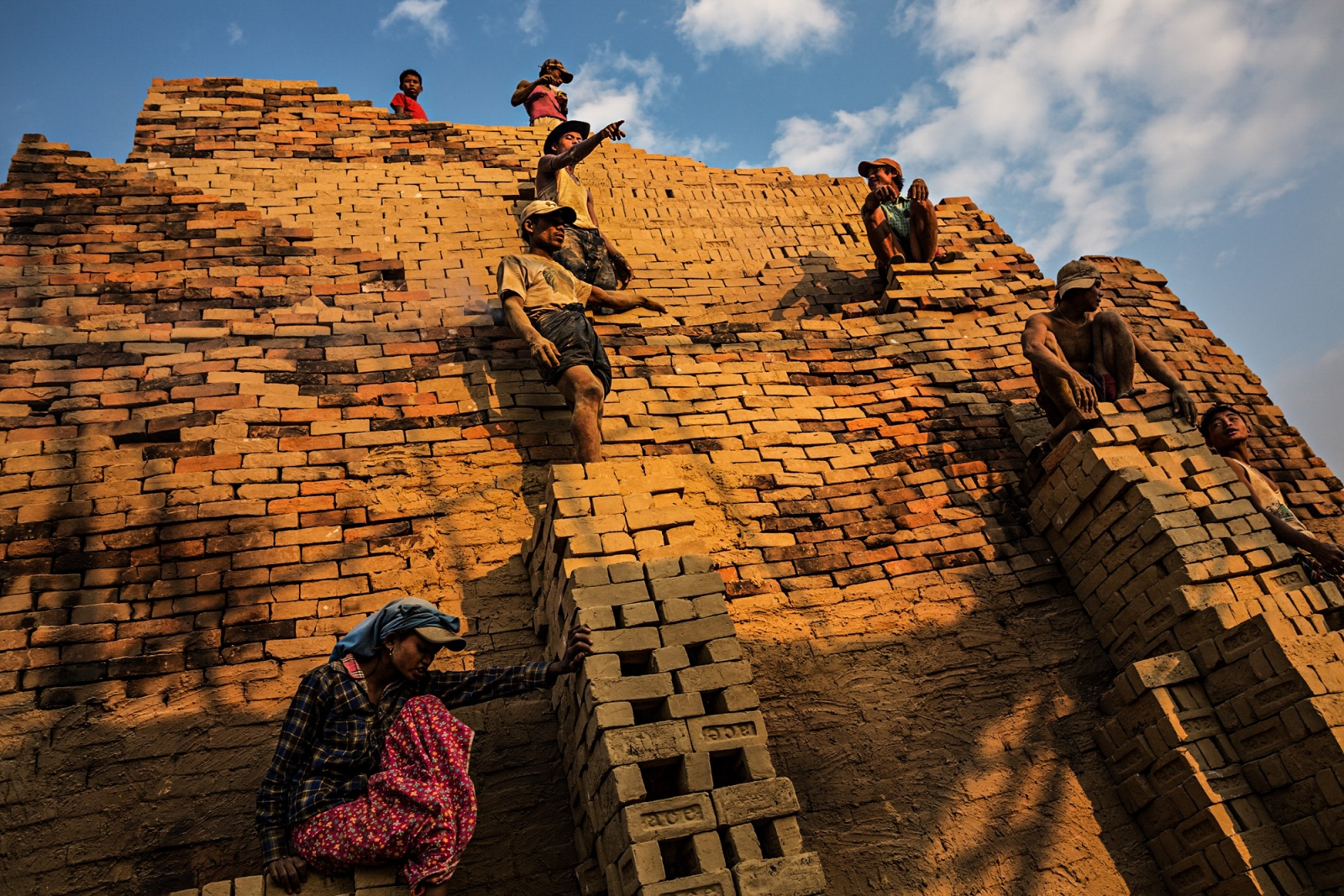 On the outskirts of Yangon, brick makers perch precariously on the side of a brick kiln in order to pass raw bricks to the top. Fires will be lit underneath the kiln and the heat and smoke will cook and dry the bricks for approximately one week.