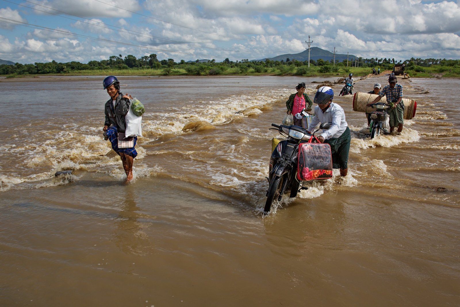 A group of travelers forge their way across a flooded road to a small village two hours from Bagan. Poor infrastructure makes rural life particularly difficult.