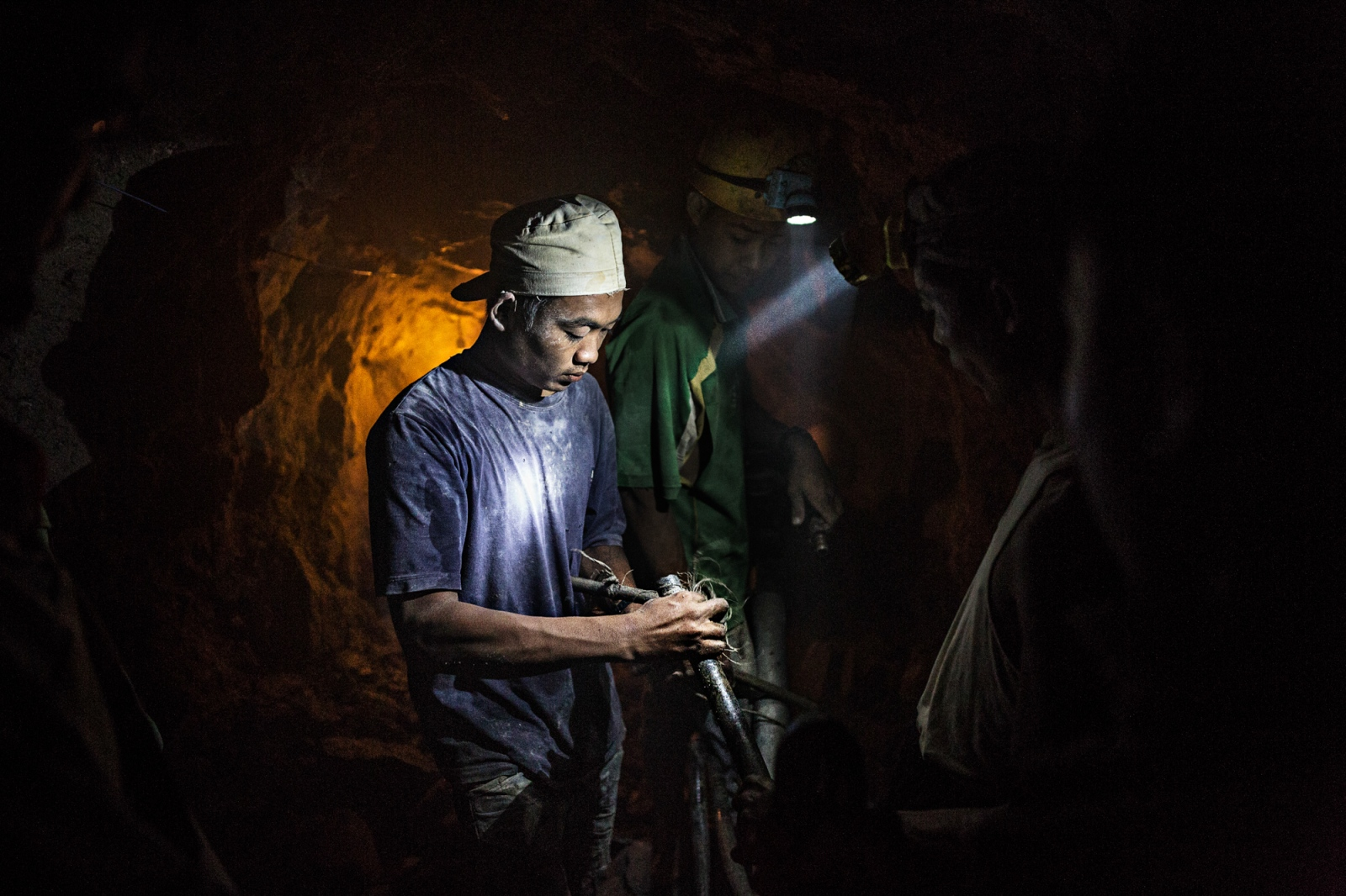 Gold miners assemble a pneumatic drill at the bottom of a mine in Singu Township. Miners