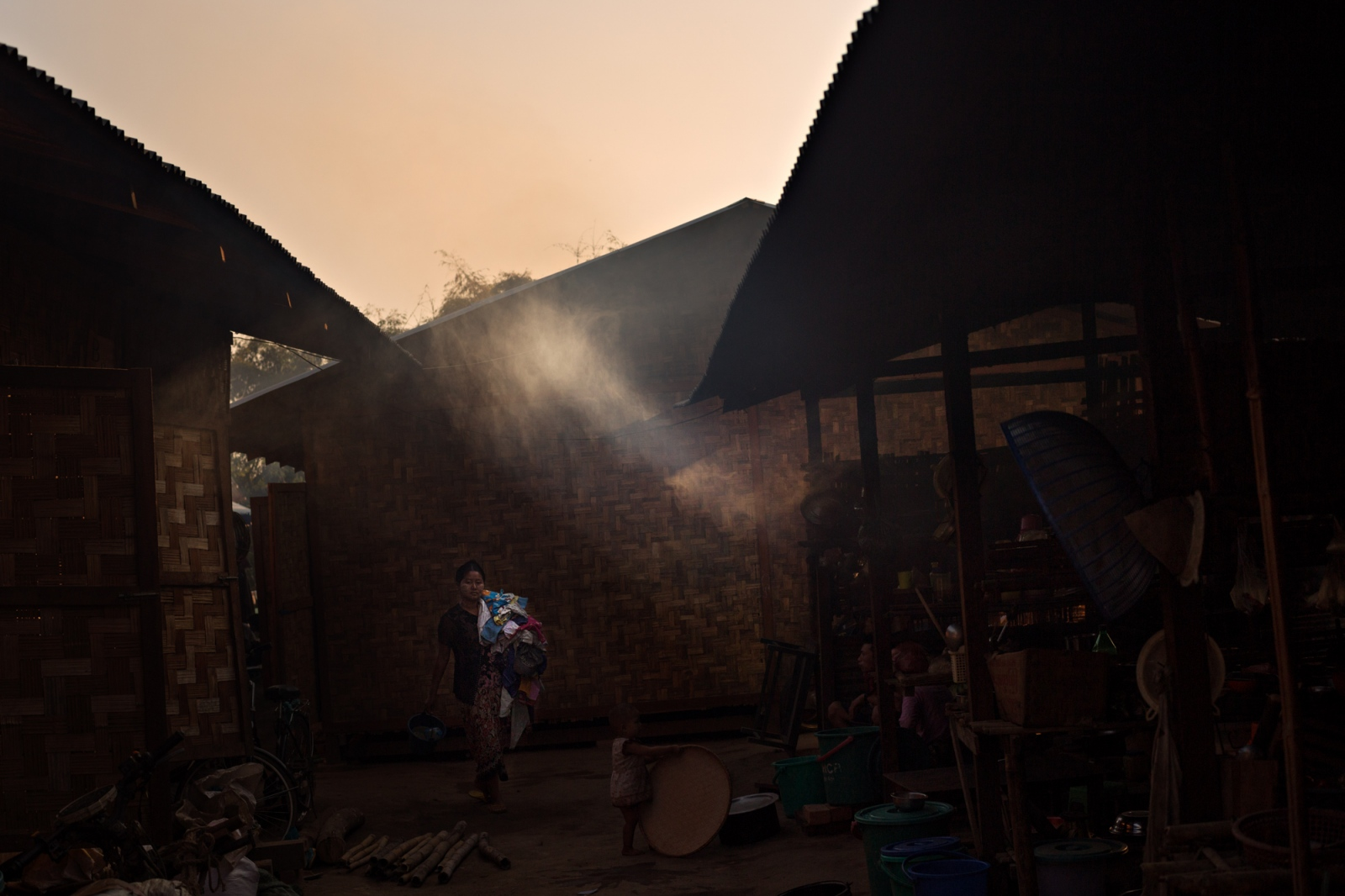 Near Mytkyina, a Kachin refugee carries laundry through the camp where she lives. Thousands of people have been displaced by conflict between the Myanmar Military and the Kachin ethnic armies.