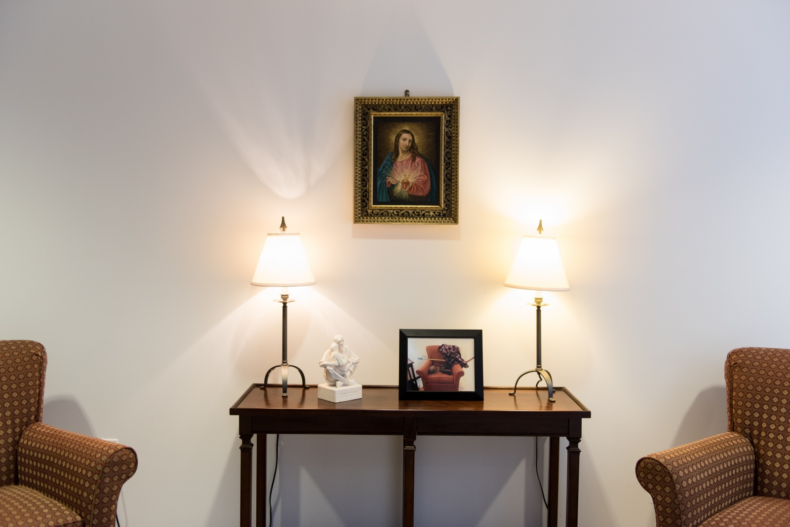 In the lobby of St. Alphonsus church in Wheeling, a picture of Jesus Christ hangs above a photograph of the empty seat adjacent to it where the church's long-time sacristan, Charlie Saad, often sat before he passed away. Several of the Wheeling area's Catholic churches have closed over the past few decades.