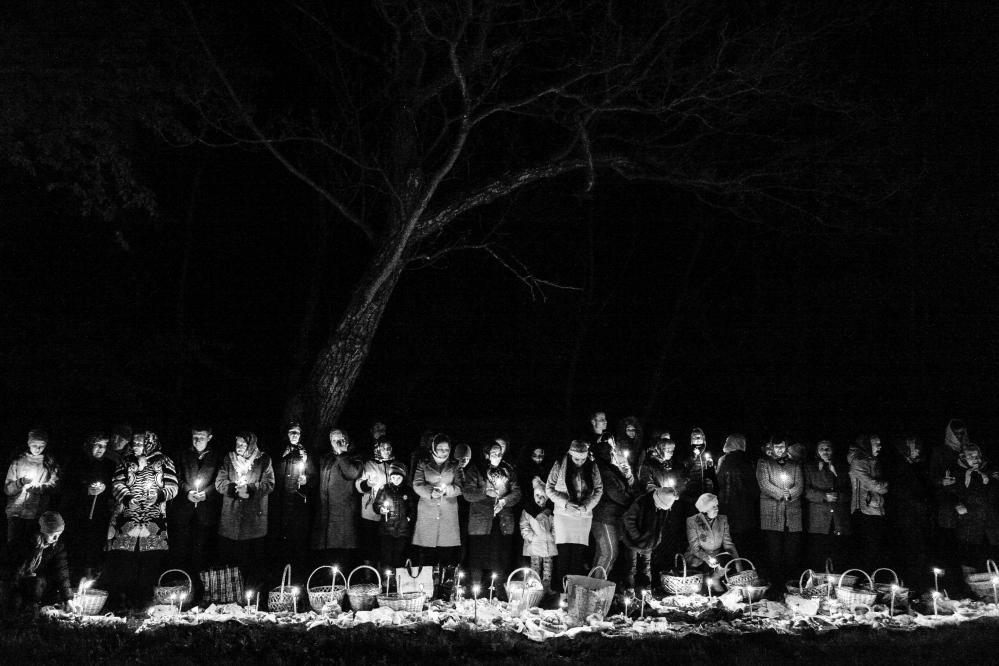 Photography image - Families from the rural village of Vadeni in Moldova wait at the local church at 4am for their baskets of food to be blessed by the local priest for the Orthodox Easter Feast.