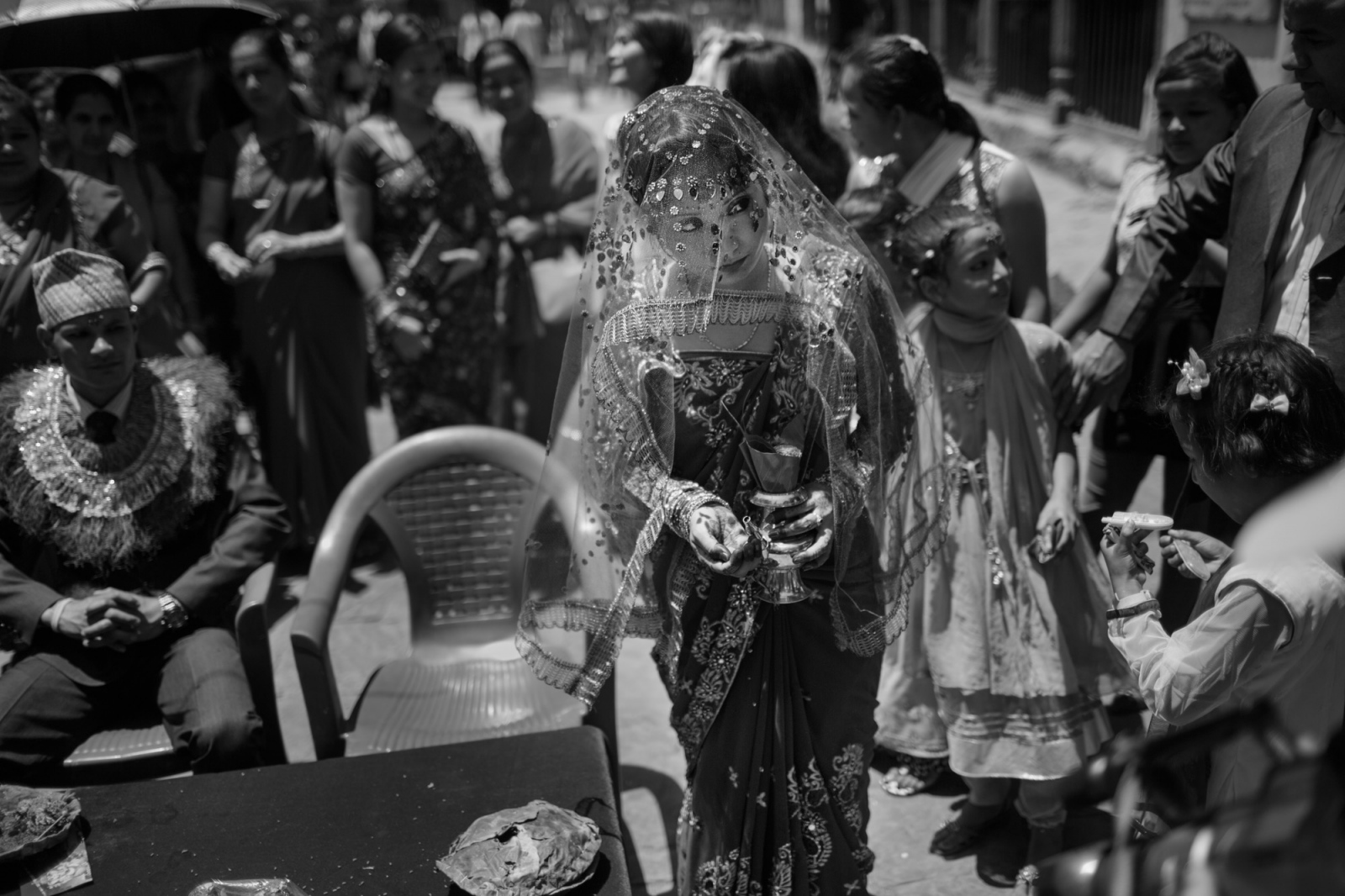 A young woman participates in a marriage ritual at a special temple in Kathmandu for couples marrying without the permission of their families. She walks around her husband (seated), dripping water on the ground as a symbol of asking the gods to protect their marriage.