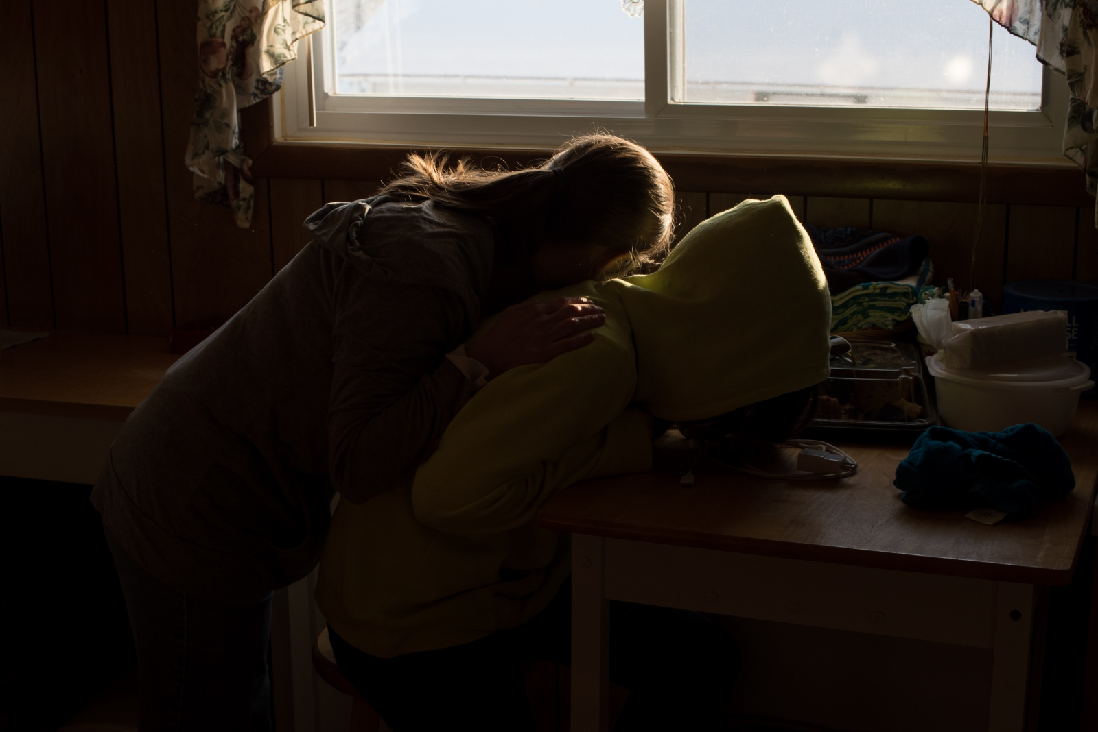 Becky Mollohan tenderly lays her head on her daughter Maddy's back in their kitchen one afternoon.