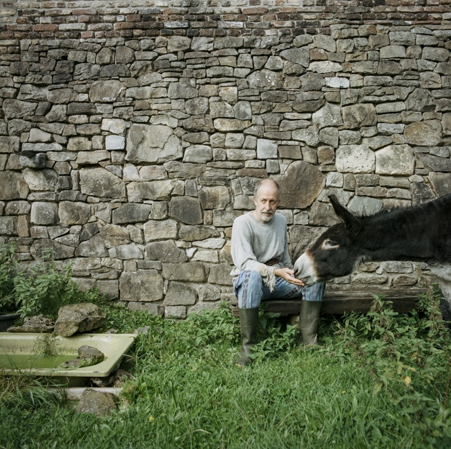 Didier poses with Bécassine. Behind the garden of his house is the farm of the three acorns. This nearly-rural space was built partly by Didier. Each evening, the inhabitants of Pierreuse are rocked by the soft donkey braying of Becassine and her son, Zorro.