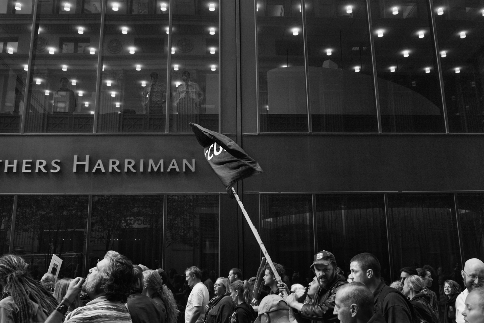 OWS protestors march past a Brown Brothers Harriman, an investment and banking firm.