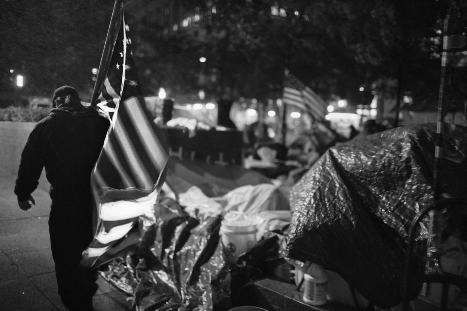 An OWS protestor carries an American flag through the rain at night, circling Zuccotti Park.