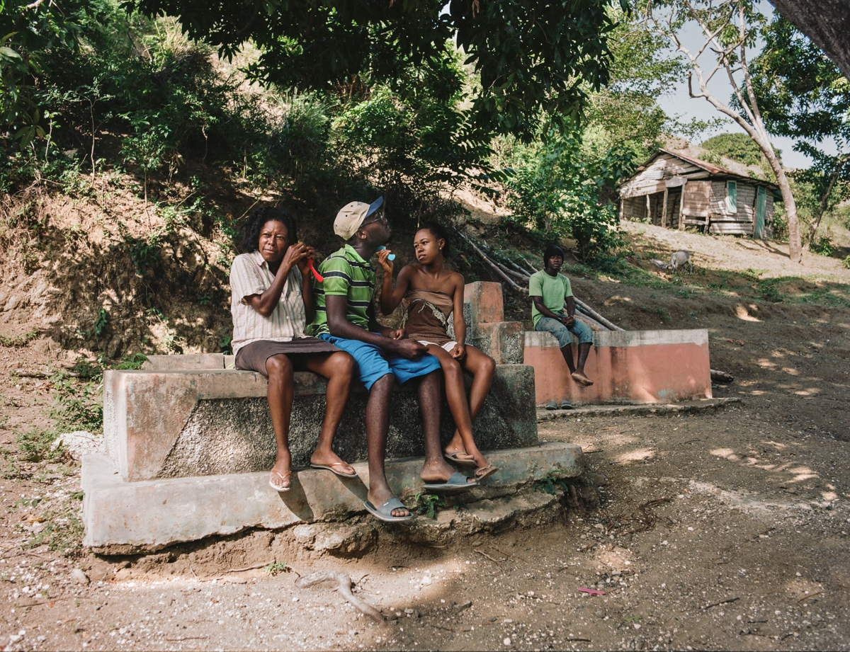 "Baobe, Haiti - Micheline (46), Francia (21), Amédé (26) Who is buried in this grave? Grandfather, three woman and a boy. Why do you like to rest there? We sit there during the heat and we enjoy the freshness. Who designed this monument? Boss Gela in 1991. ""Kavo mwe, m'rems (my vault, I love it!)"""
