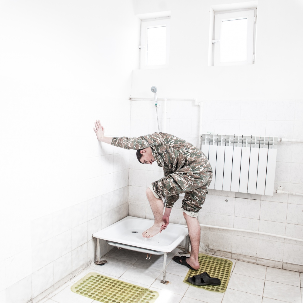A young cadet washes his feet in a dorms' bathroom of the military high-school in Stepanakert.
