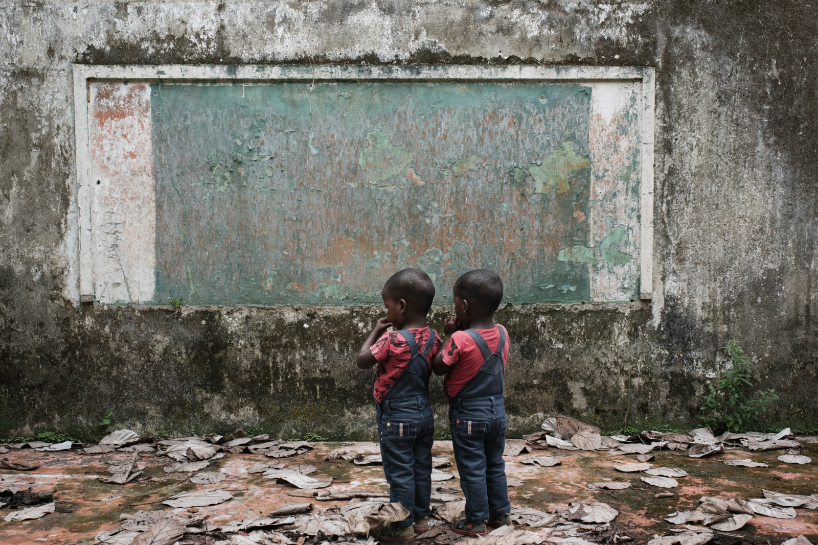 Two twins stand in front of what was once the chalkboard of one of the classrooms of Old Bellavista. May 2nd, 2017. Old Bellavista, Bojayá, Colombia.
