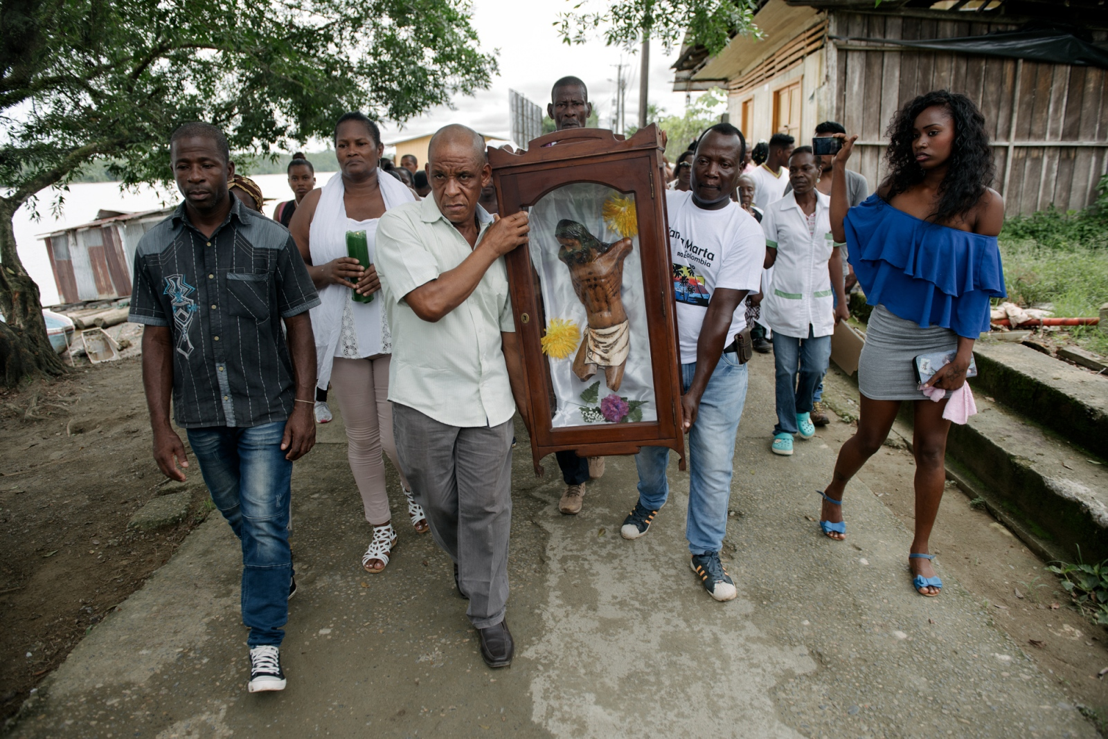 "Locals from New Bellavista carry ""the mutilated Christ"" at Vigia del Fuerte, the town that gave them shelter after the FARC perpetrated a massacre at Bellavista on May 2nd, 2002. The remains correspond to the Christ's statue that was at the church where 79 people died during the massacre of Bojayá. May 2nd, 2017. Vigia del Fuerte, Bojayá, Colombia."