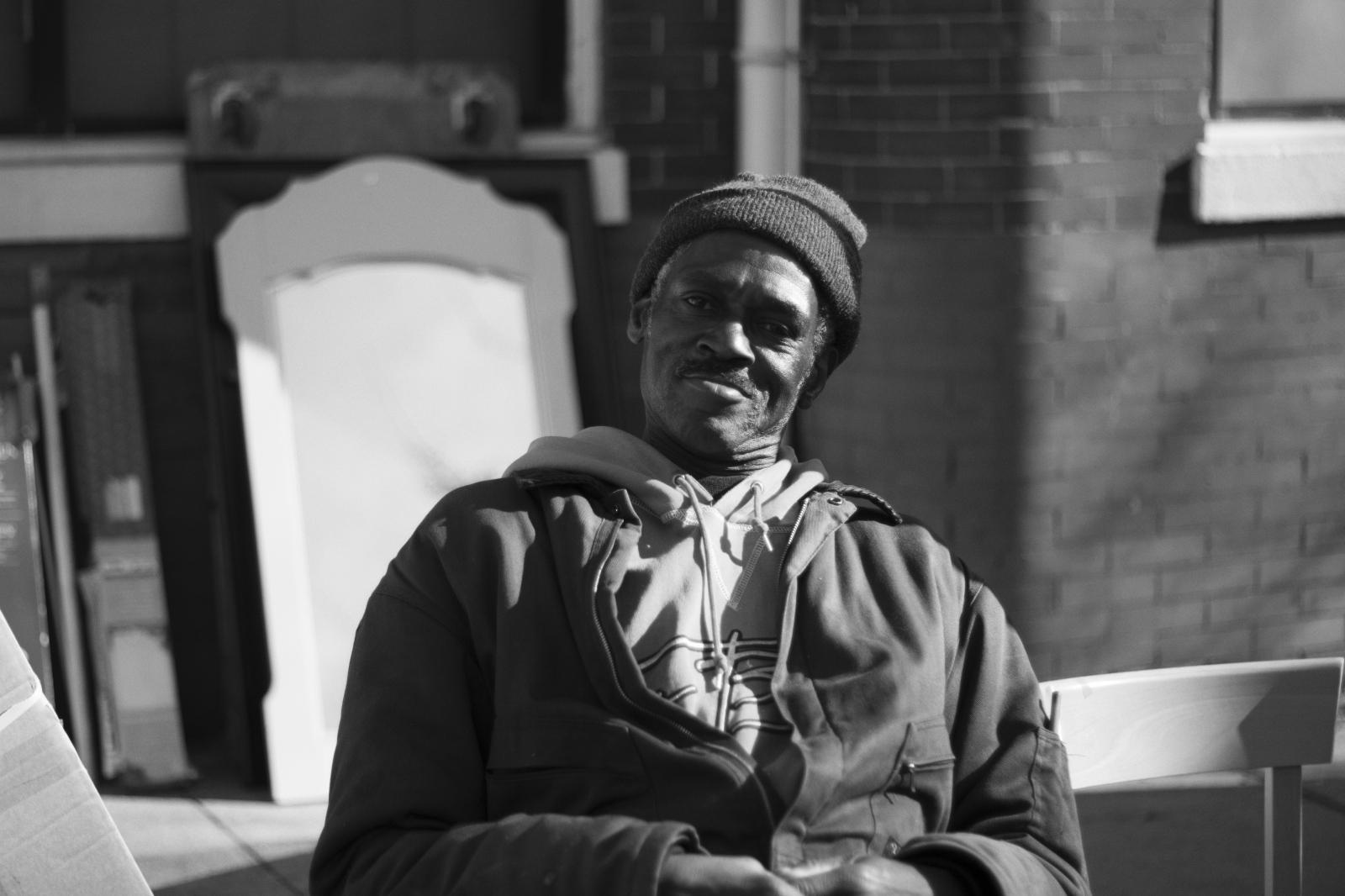 an elderly black man sitting in a chair outside