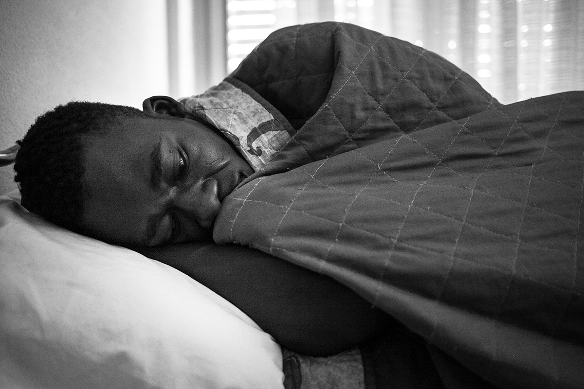 Malick lies on his bed in Hotel Colibri. He shares room with three more people from Gambia and Senegal.