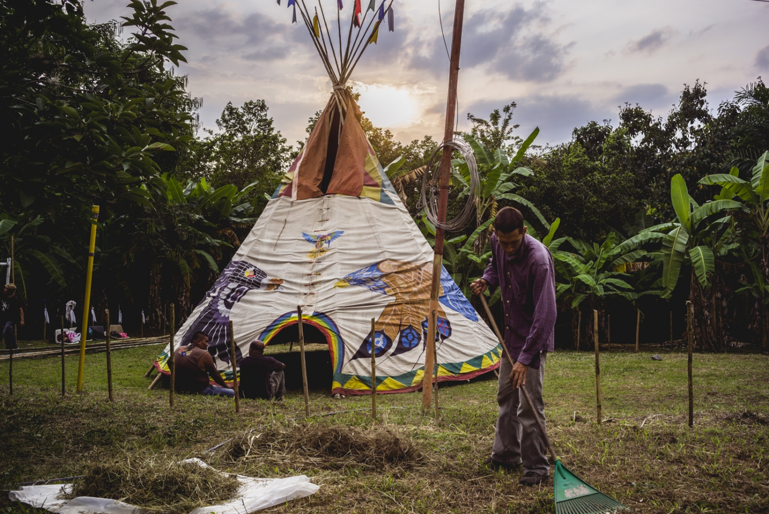 Alejandro rakes the camp grounds in preparation for the Vision Quest as the sun sets over the tipi and jungle forage.