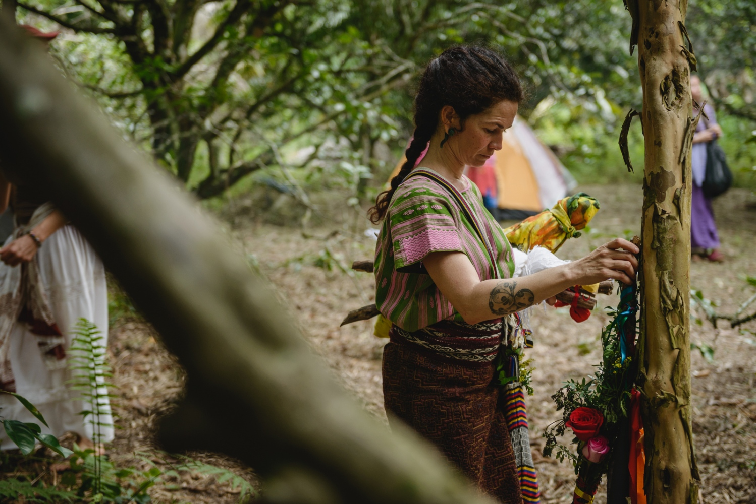 Rosa, one of the 21 visionaries who will be fasting the four days during the Vision Quest, leaves behind an offering of flowers to the spirit of the forest and the mountain.