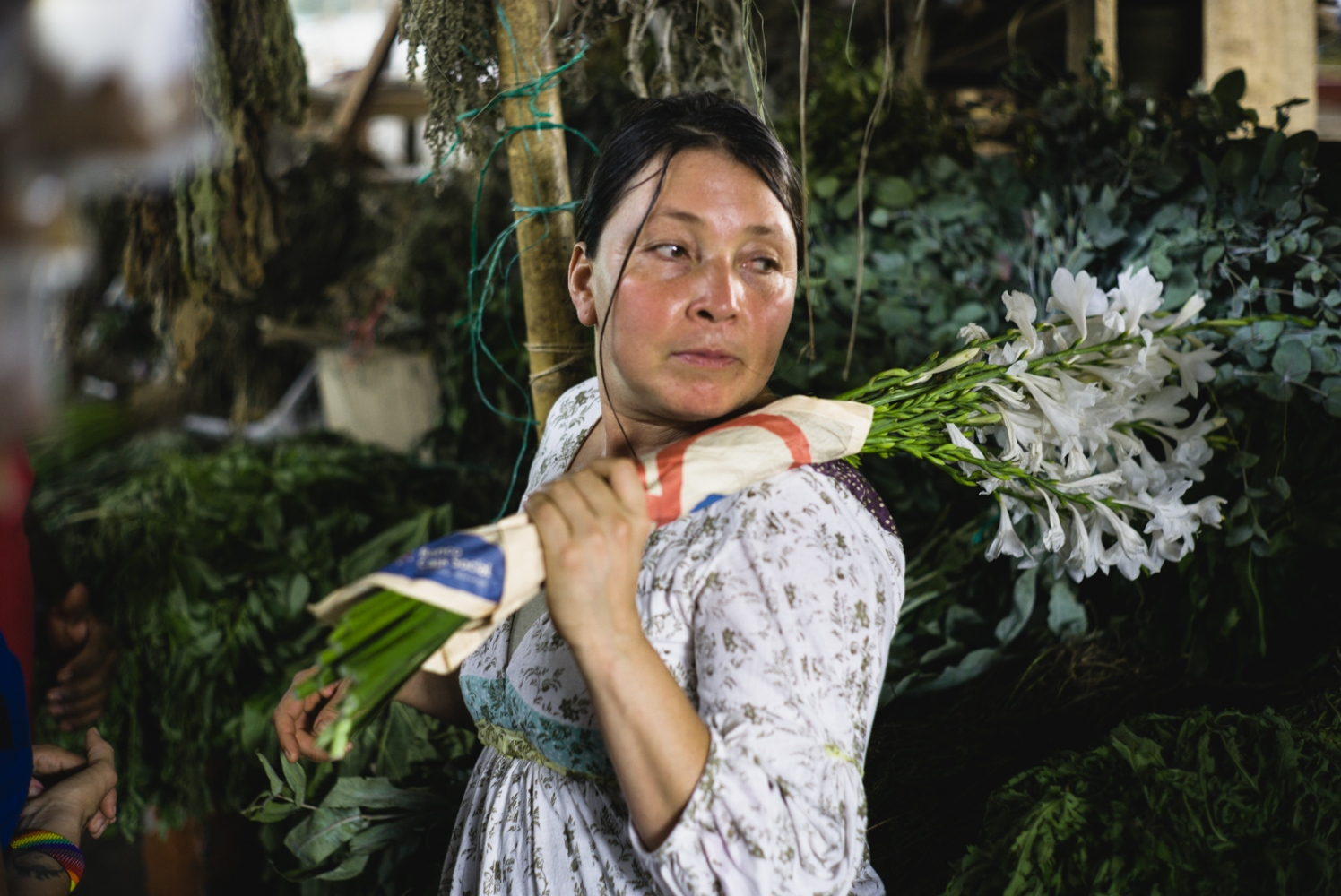 Citlali, a 'yagecera,' or traditional medicine woman, collects flowers and medicinal plants at the local market in Florida, Colombia.