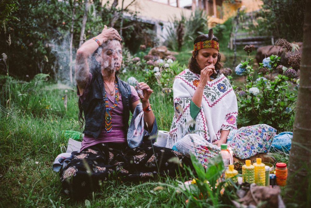 Carolina and Giscela smoke pure tobacco cigars whilst making a women's offering to the Earth outside their home in Santa Elena, Colombia.