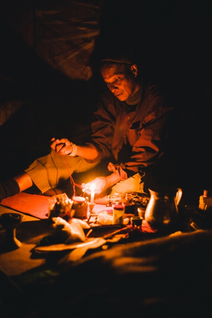 Traditional medicine man and 'Yagecero', Argemiro makes a small prayer to the medicine spirit whilst leading a yagé ceremony in the dark in Santa Elena, Colombia.