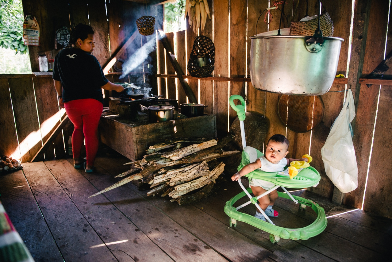 The daughter of Taita Juan prepares food with a traditional firewood stove as her baby girl plays about the kitchen. Mocoa, Putumayo, Colombia.