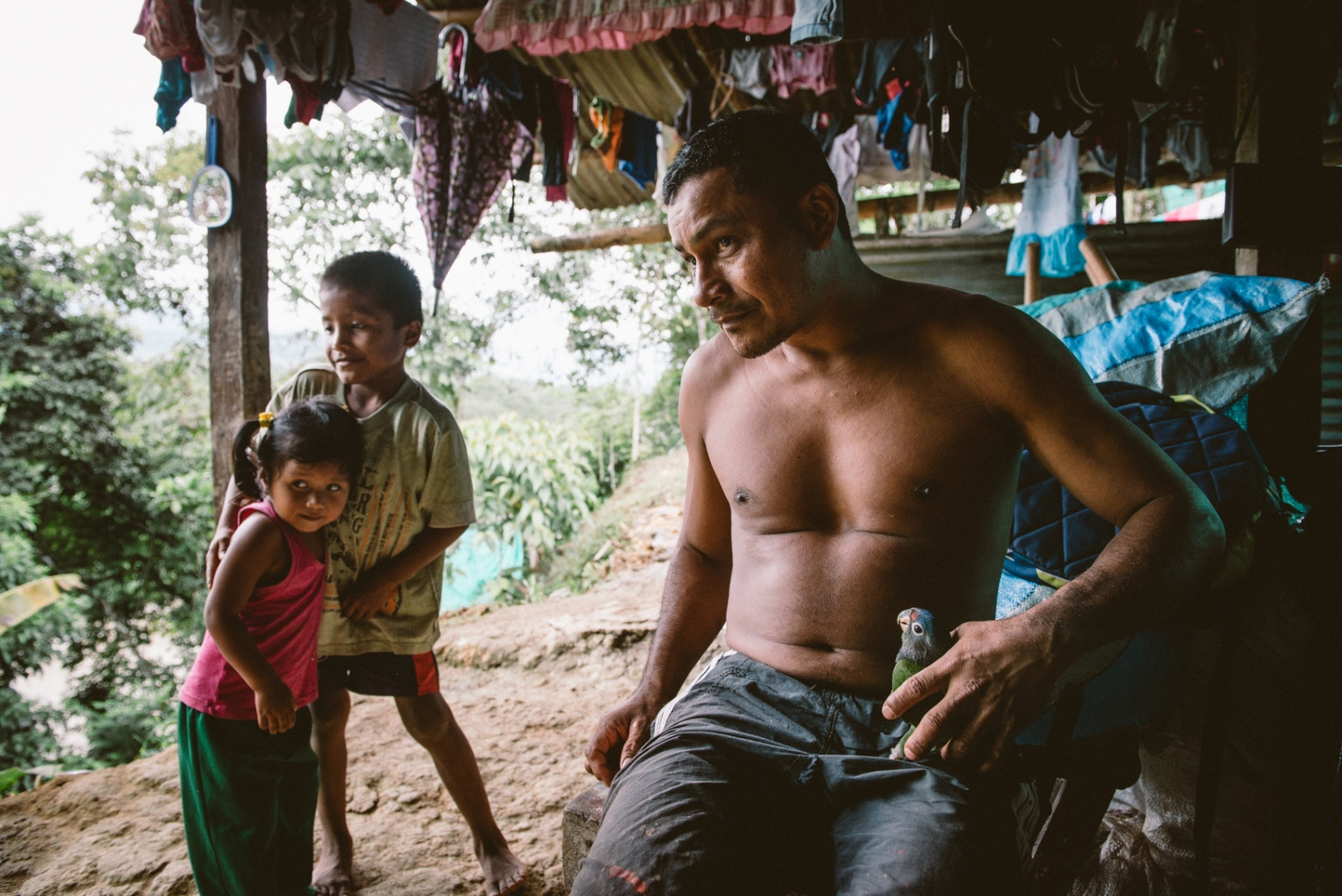 Traditional healer and medicine man, 'Taita' Carlos Chindoy and his children in their make shift home on a cliff in Mocoa, Putumayo, Colombia. Taita Carlos is a well known 'curandero' who heals his patients with the Yagé (ayahuasca) plant of the Amazons which he also prepares in a ceremonial way for his fellow community of indigenous Sciona healers.⠀