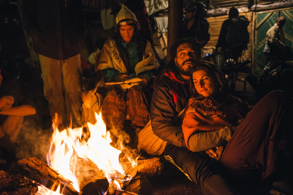 Medicine music composer Kirtan Reggae cuddles up with a foreign festival goer next to the fire during a spirituality and alternative living festival in La Calera, Colombia.
