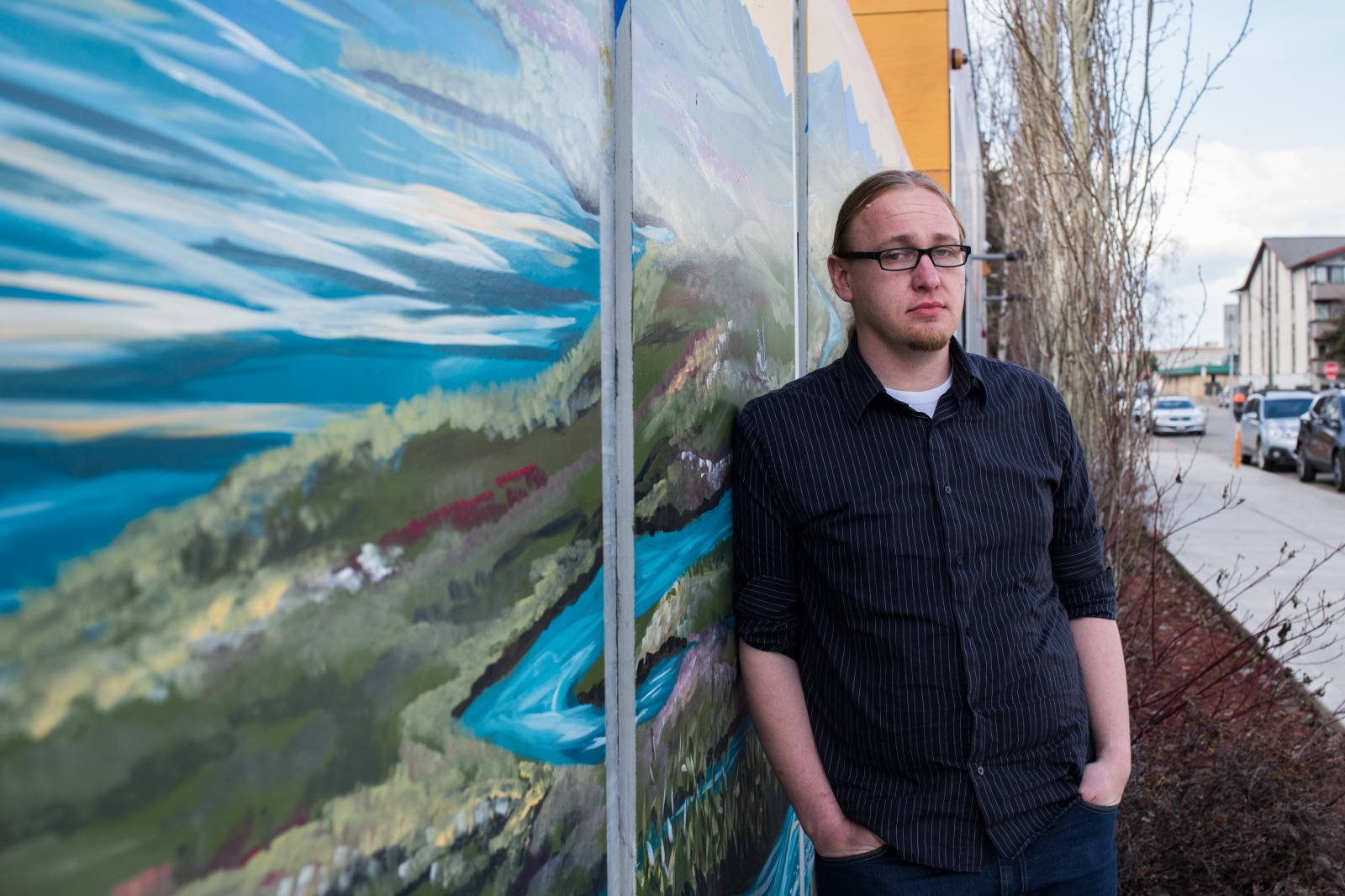 "Josh Louwerse, youth engagement program coordinator of Covenant House in Anchorage, stands outside of Covenant House in downtown Anchorage. ""We're extra vulnerable to [sex-trafficking] in Alaska for the same reasons we are vulnerable in other areas. We have historical trauma, we top the country in suicide, physical abuse, sexual abuse, and the same reasons we are vulnerable to all of those problems are the same reasons we are a vulnerable state for trafficking,"" Lowerse says. ""We also have transient male-dominated industries--millitary, oil, fishing, tourism, there'a lot of trnasient folks here. And then take those factors and put them together in rural areas, and that makes up much of our state."" Lowerse, a former youth pastor, says that he didn't intend to work neccessarily on helping victims of human trafficking, but rather that he just felt called to help at-risk kids. But as it has become more clear that human trafficking is an issue in Alaska, he says, ""we have to do something about it."""