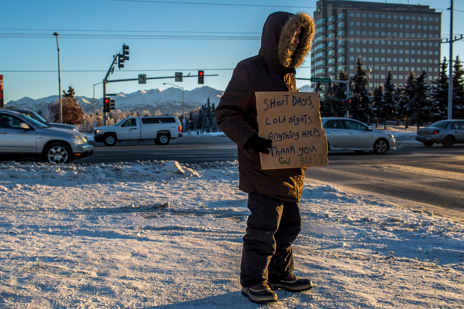 "Carl, 28, holds a sign on a corner in Anchorage on the morning December 14, 2016, when the temperature remained in single digits. Carl has been homeless for most of his life. According to him, his 20th anniversary of being homeless is coming up next month, shortly after his birthday. He says physically, the hardest part about being homeless in Anchorage is the frostbite; he typically suffers 5 bouts of frostbite each winter, and is presently suffering his second bout this season. He says he's gotten into cycles in the past of going to jail just to stay warm, which has now made getting work difficult. ""I have 29 misdemeanor thefts, so nobody is going to hire me. So I'm looking for work, but when [employers] get to the computer part, they literally laugh at me and tell me to get out of their store,"" Carl says. ""I'm not going to lie to nobody; I'm just waiting to die now."" Emotionally, he says homelessness is very difficult in Anchorage. He says people have spit on him, hit him with rocks, and often treat him like he is not even human. ""I gave up a long time ago,"" he says. He has two children, ages 8 and 12, but says he doesn't see them. ""I make sure they don't see me,"" he says."