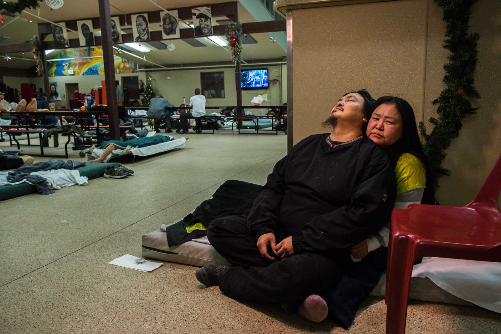 Steve Moses and Marie Nickolai sit on a mattress in Bean's Cafe, a soup kitchen which also serves as one of the men's overflow shelters in Anchorage when the shelter across the parking lot, Brother Francis Shelter, is full. Marie's half-brother, Jackie Amaktoolik, who was also homeless, died earlier that day in the parking lot. Due to the special circumstances, Bean's Cafe allowed Marie to stay the night on a mattress separated from the men's. Before lights out, however, Steven and Marie are kicked out of the shelter for drinking. For the Guardian .