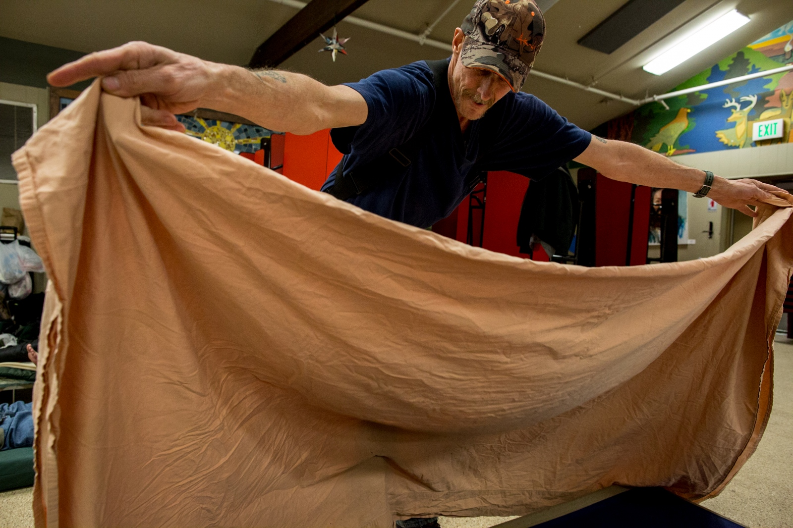 JD Hoskins, 58, makes his bed for the night at Bean's Cafe, a soup kitchen that serves also as a men's overflow homeless shelter in Anchorage. JD has been volunteering at the cafe to make sure that he has a bed for the night, and hopes to work towards self-sufficiency.