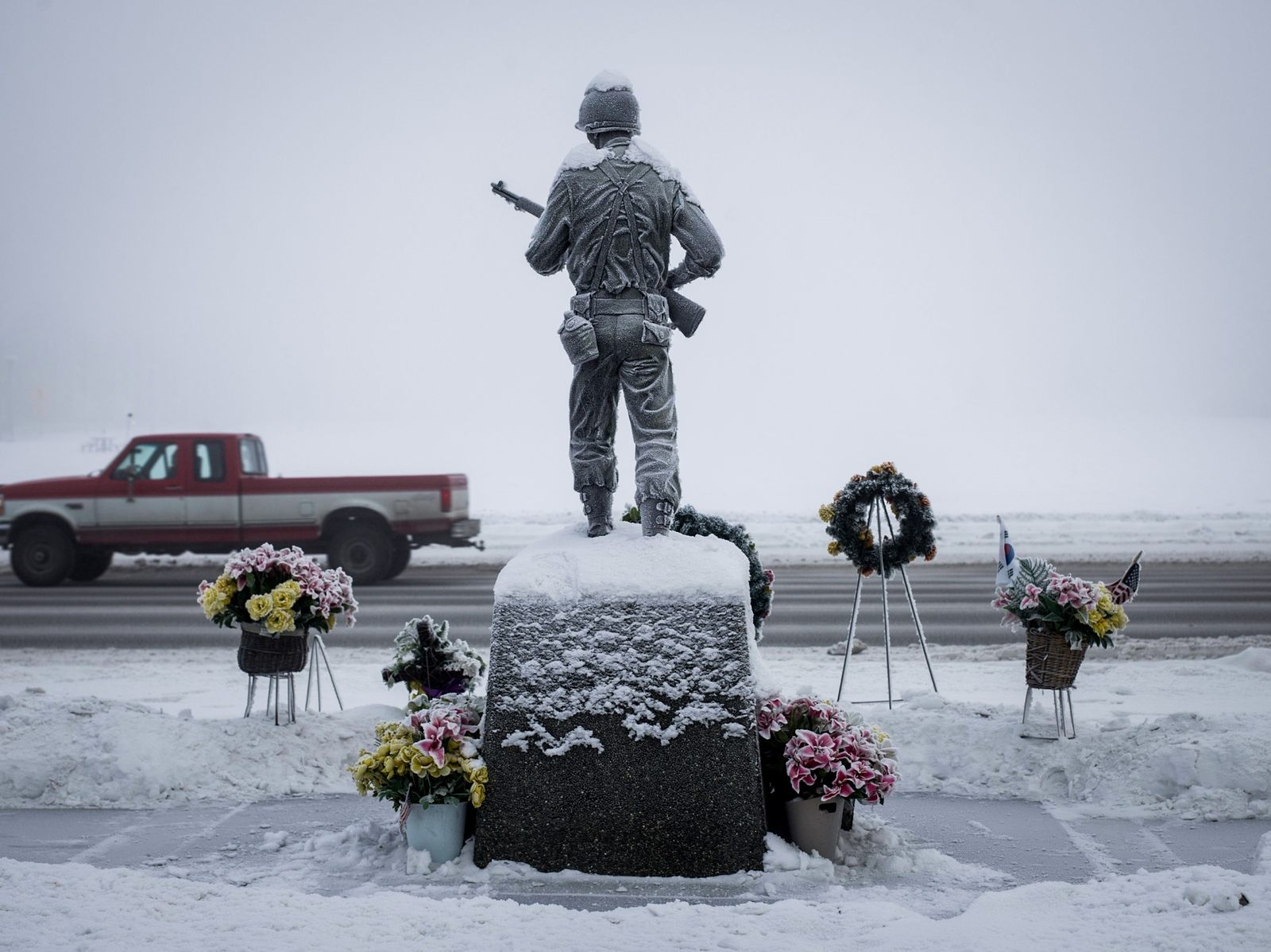 A truck drives past the Veterans Memorial on the Delaney Park Strip in downtown Anchorage on a day when the air hung thick with ice fog.