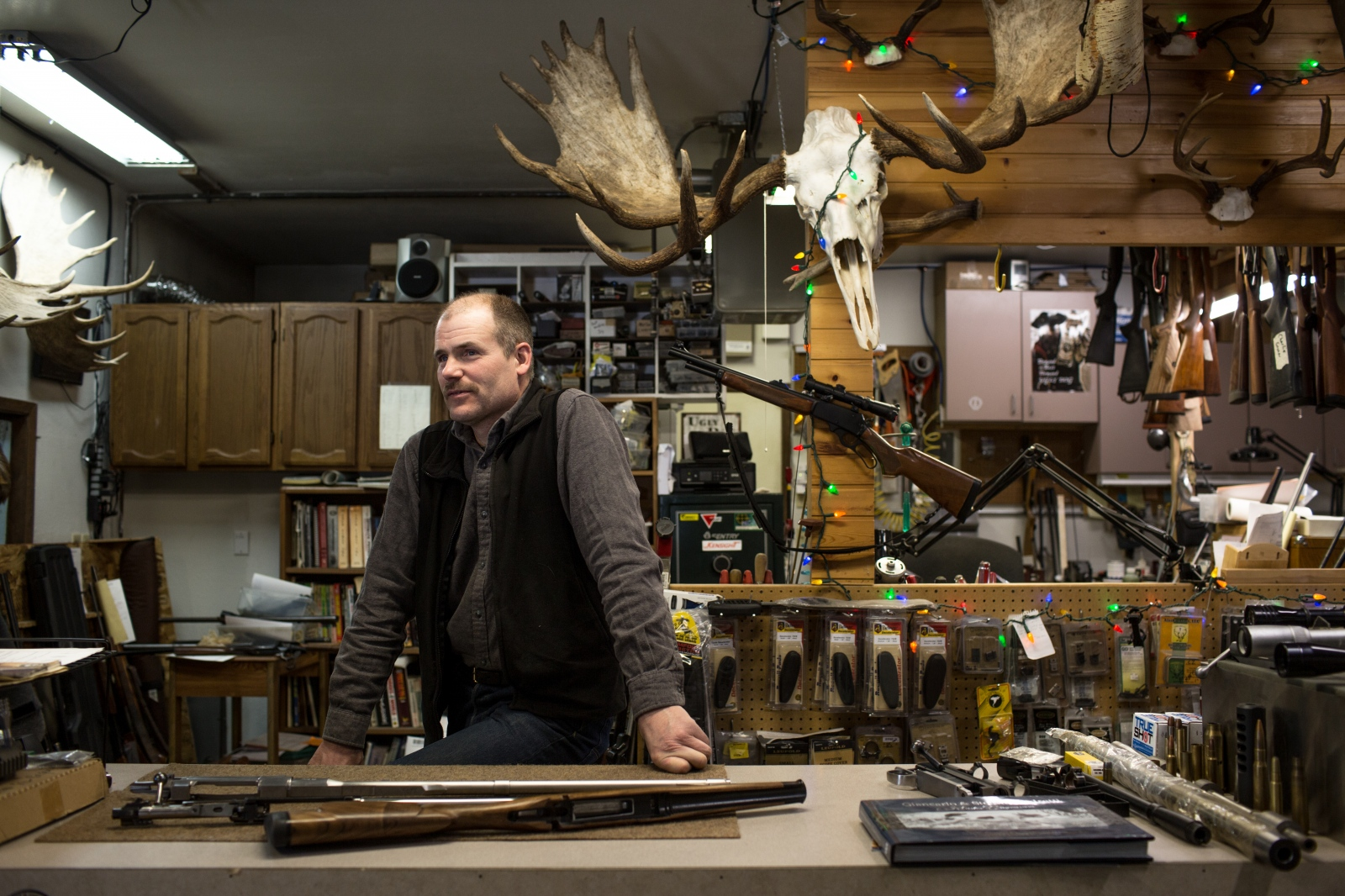 Andrew Hawk, 52, in his shop in Anchorage, Alaska. Hawk, a gunsmith, works from home along with Jen Jolliffe, an acupuncturist. Both receive healthcare coverage through the ACA and are concerned about what the AHCA for health coverage would mean for them. For KHN/the Washington Post .