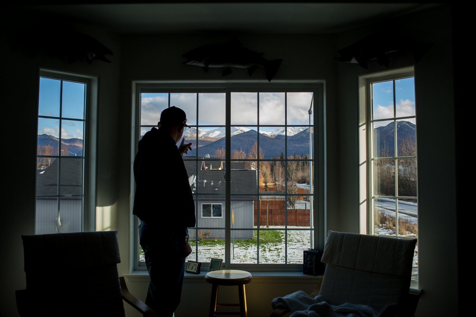 "Carl Michael, 54, gestures to the Chugach Mountains from his home in Anchorage, Alaska. ""This view is why I live here,"" he says. Michael says that health insurance is so expensive that he either has to pay for coverage or pay for his mortgage. ""It's either healthcare or my house,"" he says. ""I've worked my whole life for this house. I shouldn't have to choose."" For the Wall Street Journal ."