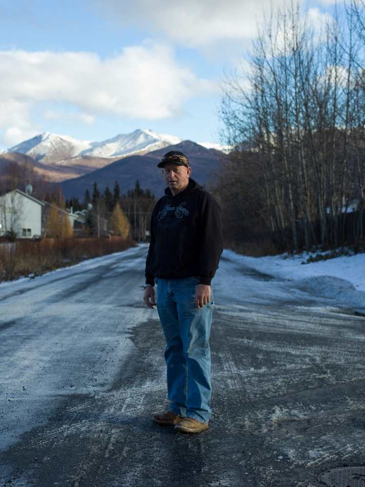 "Carl Michael, 54, on his street in Anchorage, Alaska. Michael says that health insurance is so expensive that he either has to pay for coverage or pay for his mortgage. ""It's either healthcare or my house,"" he says."